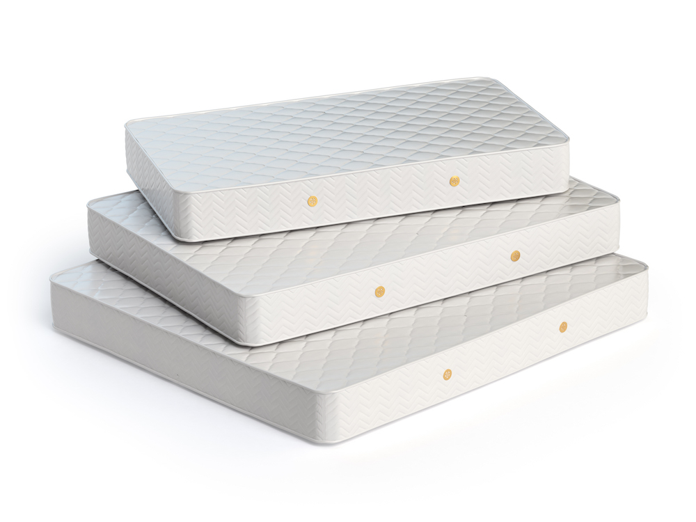 Mattress isolated on white background. Stack of orthopedic mattresses of different sizes.