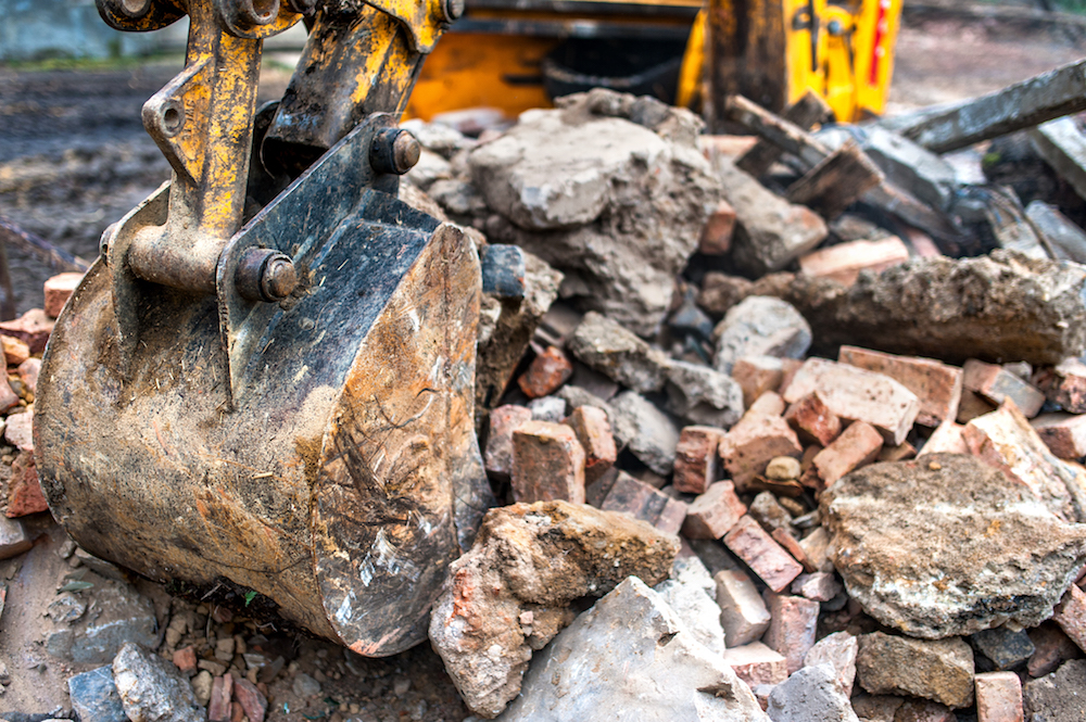 close-up of excavator bucket loading rocks, stones, earth and co