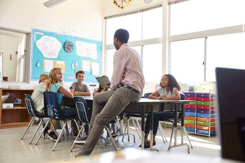 Male teacher with elementary school kids in school class