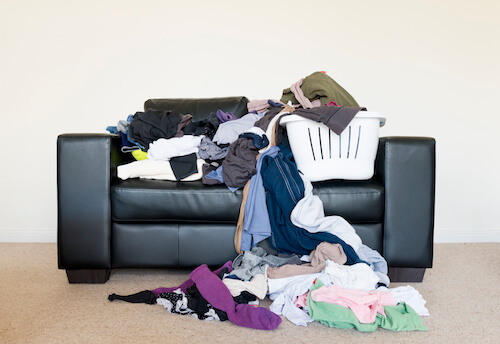 pile of clothes on sofa