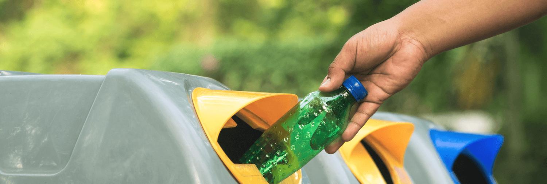 putting plastic bottle in bin