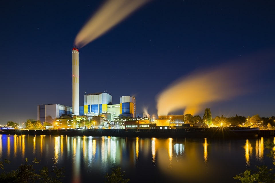 Colorful night shot of an illuminated modern industrial building with steam and deep blue sky behind a canal.