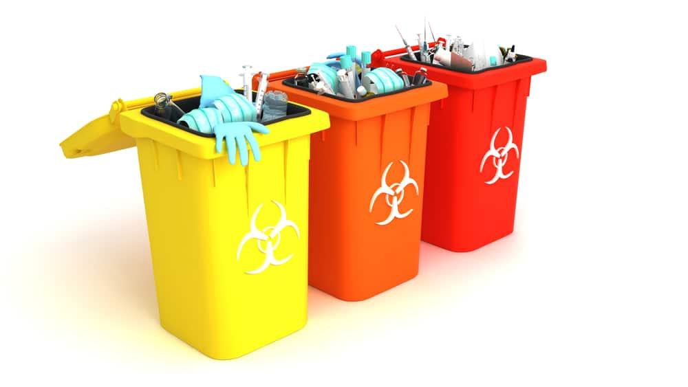Used face masks and sterile gloves in medical waste bin