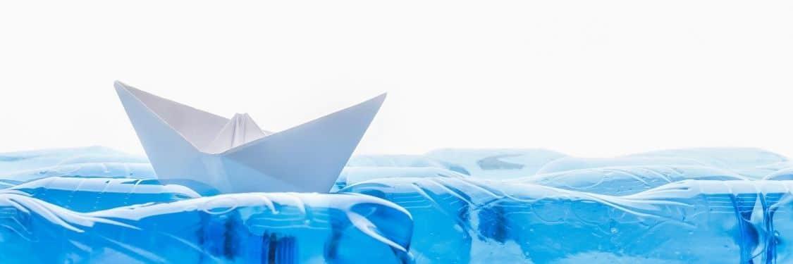 Paper boat in water of plastic bottles